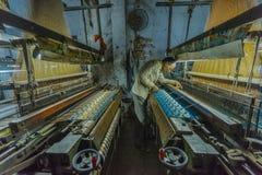 一个丝绸制造者在一家小工厂审查他的工作在瓦腊纳西,印度 免版税库存照片