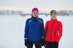 一个两个年轻人女运动员的画象在冬天冰原摆在 免版税库存图片