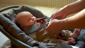 一个两个月孩子在手提物被投入,并且安全带被紧固 孩子镇静地看 影视素材