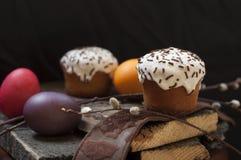 一个两小复活节蛋糕和被洗染的鸡蛋和一根杨柳枝杈在黑暗的木背景 免版税库存图片