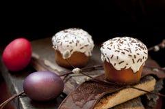一个两小复活节蛋糕和被洗染的鸡蛋和一根杨柳枝杈在黑暗的木背景 库存照片