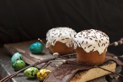 一个两小复活节蛋糕和被洗染的鹌鹑蛋和一根杨柳枝杈在黑暗的木背景 免版税库存图片