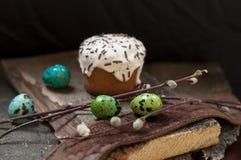 一个两小复活节蛋糕和被洗染的鹌鹑蛋和一根杨柳枝杈在黑暗的木背景 库存图片