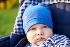 一个严肃的小男孩的画象坐在摇篮车的盖帽的户外 库存图片