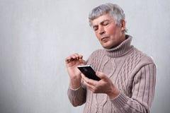 一个严肃的成熟人在他的手上的拿着智能手机看殷勤地入屏幕 老人读书在电话的正文消息 图库摄影