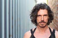 一个严肃的被刺穿的人的画象有胡子和长的头发的 免版税库存图片