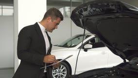 一个严肃的车商在本文描述汽车的细节 免版税图库摄影