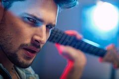 一个严肃,英俊的吉他弹奏者的画象 库存图片