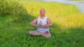 一个中间年迈的人早晨做呼吸的瑜伽并且思考在湖 影视素材