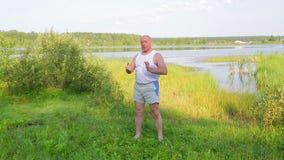 一个中间年迈的人早晨做在湖的呼吸的瑜伽 影视素材