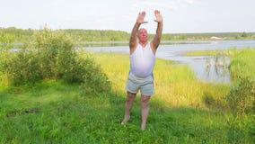 一个中间年迈的人早晨做在湖的呼吸的瑜伽 股票录像