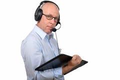 一个中年人与一种数字式片剂和耳机一起使用 免版税库存照片