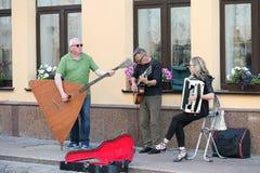 一个乐团在一条老欧洲街道上的三人 带包括两个人和一个女孩 有低音提琴和a的人 库存照片