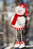 一个乐趣雪人,垂悬在分支的圣诞老人 免版税图库摄影