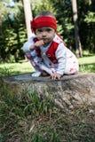 一个九个月女婴的画象一个红色头饰带的坐一个树桩在一个绿色夏天公园 库存照片