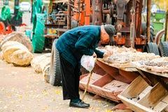 一个买石头的年长人尝试在默阿布存放,当它时 免版税库存图片
