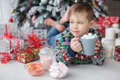 一个五岁的男孩在拿着一杯大咖啡的一棵美丽的圣诞树旁边说谎用蛋白软糖 库存图片