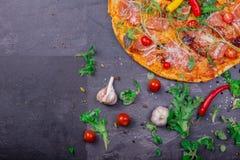 一个五颜六色和内容丰富的薄饼的一张顶视图用红色蕃茄、乳酪和辣调味汁在深灰背景 库存图片
