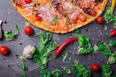 一个五颜六色和内容丰富的薄饼的一张顶视图用红色蕃茄、乳酪和辣调味汁在深灰背景 免版税图库摄影