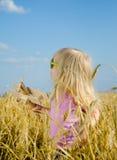 一个五颜六色的帽子和太阳镜的逗人喜爱的小女孩 免版税库存图片