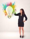 画一个五颜六色的电灯泡的小姐 免版税库存图片