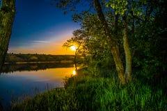一个五颜六色的风景,大月亮,在一条河的日出在树下,一个安静的夏天,一个春日 自然的5月颜色 免版税库存图片