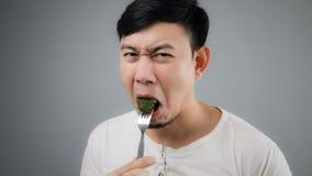 一个亚裔人吃硬花甘蓝 库存照片