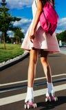 一个亚裔女孩的夏天画象夏天明亮的成套装备的有在溜冰鞋摆在的一个桃红色背包的 安赫莱斯los 库存照片