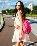 一个亚裔女孩的夏天画象明亮的成套装备和太阳镜的有在路的一个桃红色背包的 安赫莱斯los 库存照片