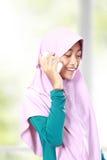 一个亚洲回教孩子的画象谈话在手机 免版税图库摄影