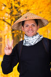 戴一个亚洲圆锥形帽子和做在autum的一个英俊的西班牙年轻企业人的画象一个胜利信号 免版税库存图片