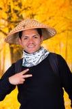 戴一个亚洲圆锥形帽子和做在autum的一个英俊的西班牙年轻企业人的画象一个胜利信号 图库摄影