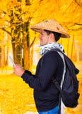 戴一个亚洲圆锥形帽子和在他的手上的一个英俊的西班牙年轻企业人的画象举行他的Ipad  免版税库存图片