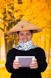 戴一个亚洲圆锥形帽子和在他的手上的一个英俊的西班牙年轻企业人的画象举行他的Ipad  免版税库存照片
