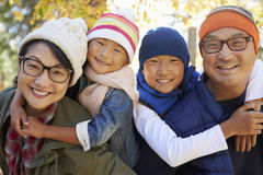 一个亚洲家庭的画象与扛在肩上父母的两个孩子的 库存图片