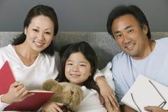 一个亚洲家庭的画象在床上在家 免版税库存照片