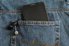 一个亭亭玉立的电话和耳机在斜纹布的一个口袋 免版税库存图片