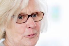 一个亲切的老妇人佩带的玻璃 免版税库存图片