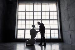 一个人与一个机器人在手中沟通,有纸板箱的 概念发运查出的白色 机器人的剪影反对的 免版税库存图片
