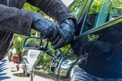 一个人与设法打破一辆汽车的锁有螺丝刀的 图库摄影