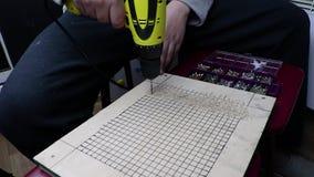 一个人与钻子胶合板的钻孔 的概念与木头和体力活儿一起使用 录影有workin的声音 股票视频