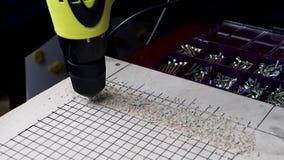 一个人与钻子胶合板的钻孔 的概念与木头和体力活儿一起使用 录影有workin的声音 股票录像