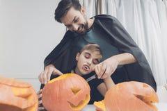 一个人为万圣夜帮助作为妖怪打扮的一个男孩切一个可怕南瓜 免版税库存图片