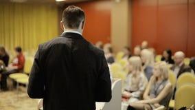 一个人举行讲话对观众在经济的大会的观众席并且提供经费给他们的事务和 影视素材