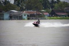 一个人乘坐红色喷气机滑雪的和飞溅在河的中心浇灌 免版税库存照片