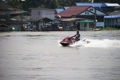 一个人乘坐红色喷气机滑雪的和飞溅在河的中心浇灌 图库摄影