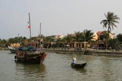 一个人乘小船穿过一条河在会安市(越南) 图库摄影