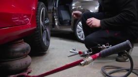 一个人使用一台起重器并且从汽车去除轮子 人的手松开螺栓,并且坚果从去除轮子 影视素材
