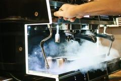 一个人修理在咖啡馆的一个残破的咖啡机器 有蒸汽,错误工作 支持和修理 免版税图库摄影