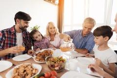 一个人倒他的家庭的汁液,聚集在感恩的一张欢乐桌上 免版税库存图片